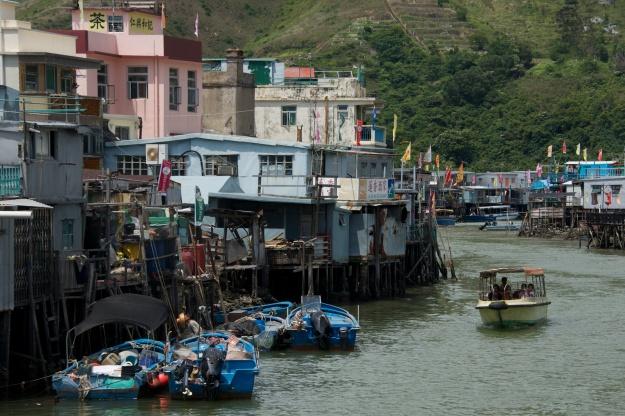 Pleasure boat passing moorings of stilted houses
